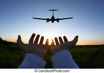 raised hands on the background of a passenger plane flying at sunset