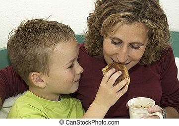 Boy giving his mommy a bite of his raisin bun.