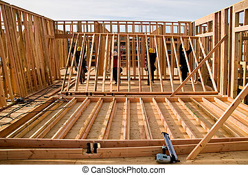 Raising a Wall - Four workmen raising a new stud wall.