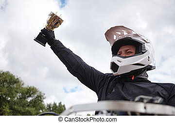 Raising hand with motorcycle competition cup