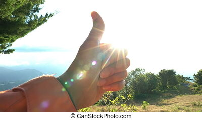 Raising hand with thumbs-up on clear blue sky background...