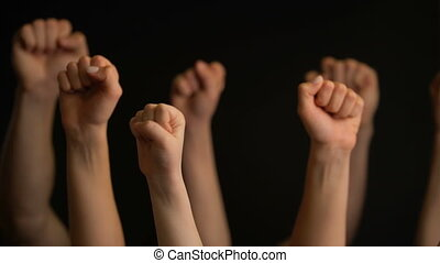 Raising hands with fists on black background. - Raising...