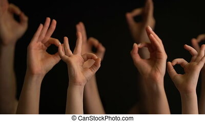 Raising hands with OK gestures on black background.
