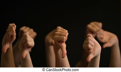 Raising hands with thumbs down on black background. -...