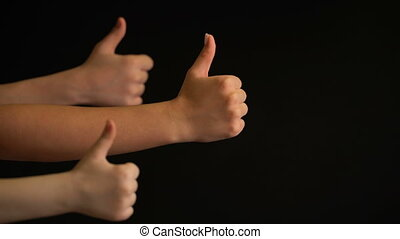 Raising hands with thumbs up on black background. - Raising...