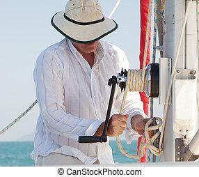 Raising the Sail - The captain of a yacht raising the...