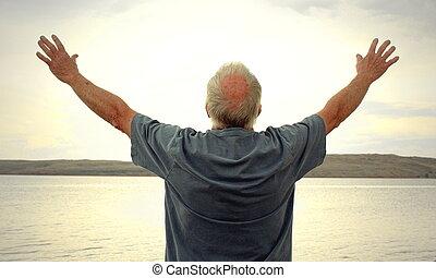 Raising the Sun - A man joyously holding his arms up toward...
