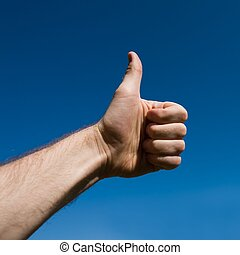 raising thumb up with blue sky at background