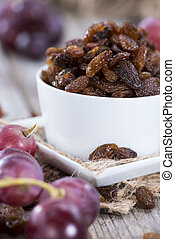 Raisins and Grapes on wooden background