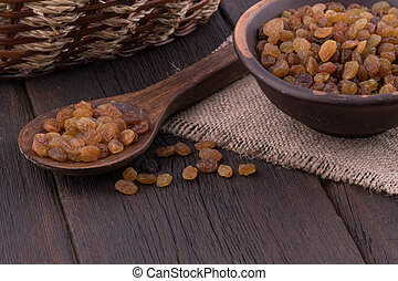 Raisins in a ceramic bowl on old wooden table.