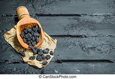 Raisins in a wooden scoop.