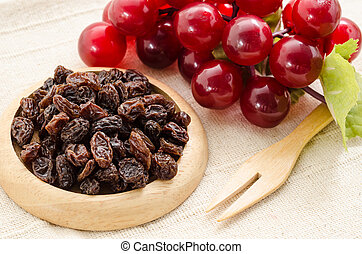 Raisins on a wooden dish and fresh red grapes.
