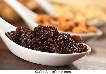 Raisins on ceramic spoon (Selective Focus, Focus on the ...