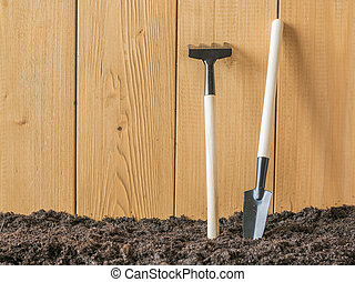 Rake and shovel at the wooden wall on the ground.