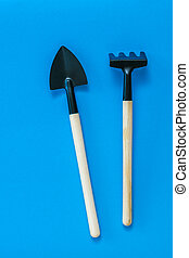 Rake and shovel for cultivating soil on a blue background.