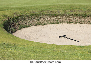 Rake in a bunker - Sand bunker on the golf course with a...