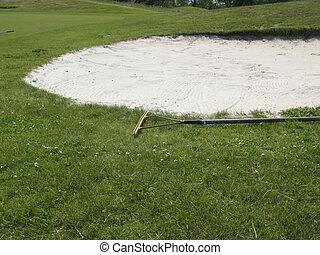 Rake near bunker on golf course