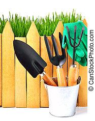 rake, shovel, rubber gloves in the pot against the wooden fence isolated on white