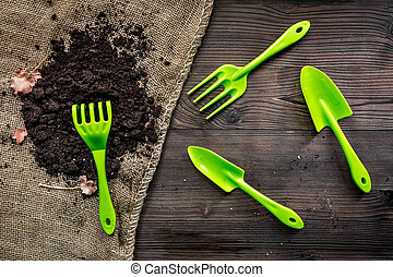 rake, trowel, ground for gardening on wooden background top view