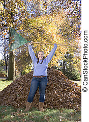 Raking Leaves Triumphant Girl - A teenage girl stands...