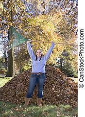 Raking Leaves Triumphant Girl - A teenage girl stands...