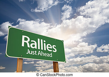 Rallies Green Road Sign Against Clouds