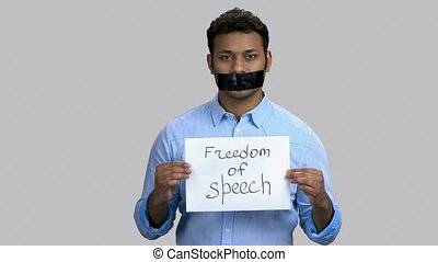 Rally activist for freedom of speech. Portrait of dark-skinned guy with taped mouth, grey isolated background.