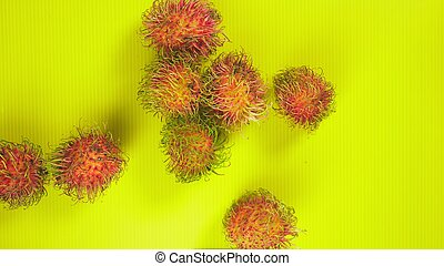 Rambutan fruits on a bright yellow background. Minimal fruit concept.