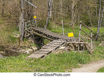 Improvised ramshackle wooden self-made bridge over a rivulet in sunny ambiance
