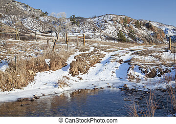 ranch road crossing stream in a mountain valley, winter ...