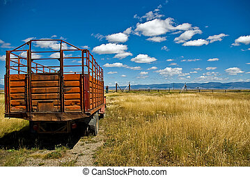 A cattle truck with red stake sides sits in a ranch meadow.