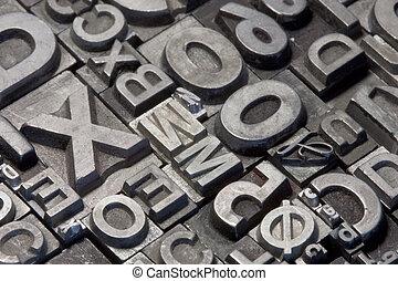 Random arrangement of letterpress lead letters in block