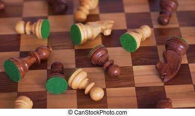 Randomly scattered wooden chess pieces on a chessboard. Video with rotation