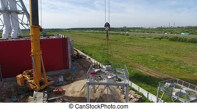 ?rane lift a chimney pipe segment for gas power plant aerial, highway at the back