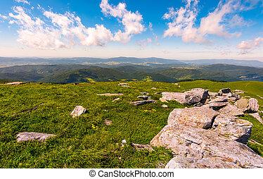 range of flat rocks on a grassy slope. beautiful summer...