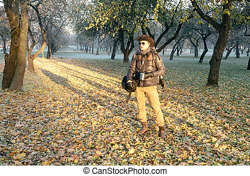 Ranger in the city park in the cold fall morning with mug...