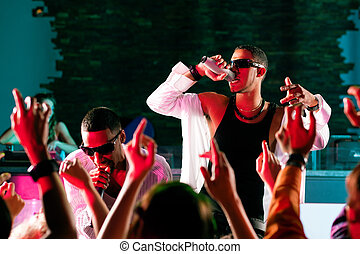 Rap or Hip-Hop Musicians performing on stage in a club in front of a cheering crowd