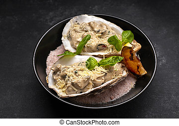 Rapana meat in a creamy cheese sauce in a shell, on a plate, on a dark background