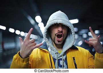 Raper gesture - Portrait of young man in hoodie showing...