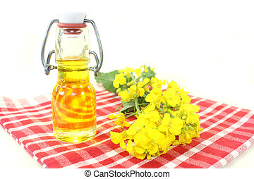 a bottle of rapeseed oil and rapeseed flowers against white background