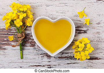 Rapeseed oil and flower. - Rapeseed oil in heart shaped bowl...