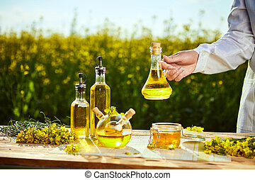 rapeseed oil bottle in hand of an agronomist or biologist on background rape field