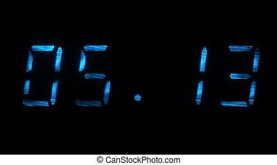 Rapid adjustment of time on the digital clock display, blue digits on a black