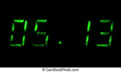 Rapid adjustment of time on the digital clock display, green digits on a black