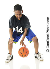 A preteen athlete rappidly dribbling his basketball close to the floor. Motion blur on hands and ball. On a white background.