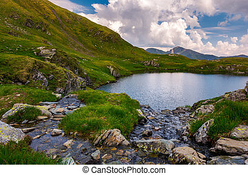 rapid streams flow to lake Capra in mountains. Fagaras...