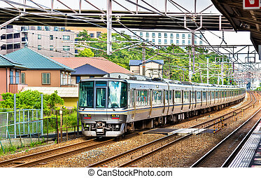 Rapid train is passing Maiko station, Japan