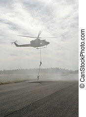 Rappelling from Chopper - Two military guys rappel from a...