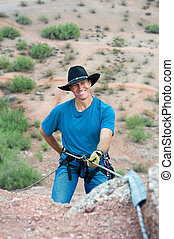 Rappelling rock climber