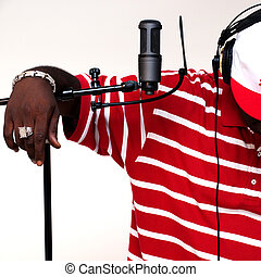 african american male artist wearing headphones in studio with microphone